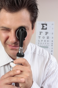 eye_doctor_looking_through_an_opthalmoscope_